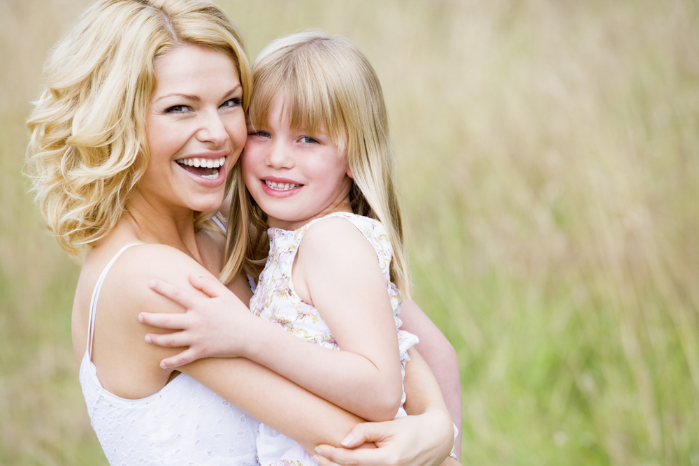 Mother holding daughter outdoors smiling